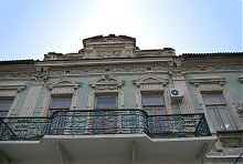 Балкон другого ярусу і вензель будинку Мінаш в Мелітополі